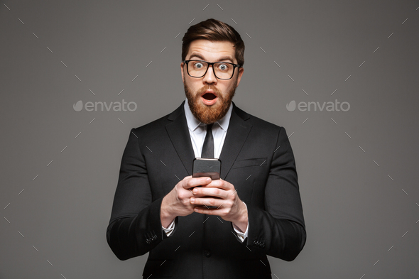 Portrait of an excited young businessman dressed in suit - Stock Photo - Images