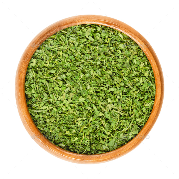 Dried parsley in wooden bowl over white - Stock Photo - Images