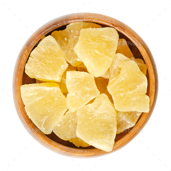 Candied pineapple pieces in wooden bowl over white - Stock Photo - Images