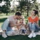 Happy Family Is Enjoying a Day in the Park. Mother Father and Sweet Little Daughter Are Smiling - VideoHive Item for Sale
