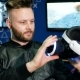 Young Man Looks at Virtual Reality Glasses Holding Them in His Hands - VideoHive Item for Sale