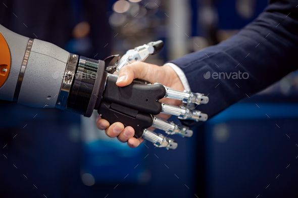 Hand of a businessman shaking hands with a Android robot. - Stock Photo - Images
