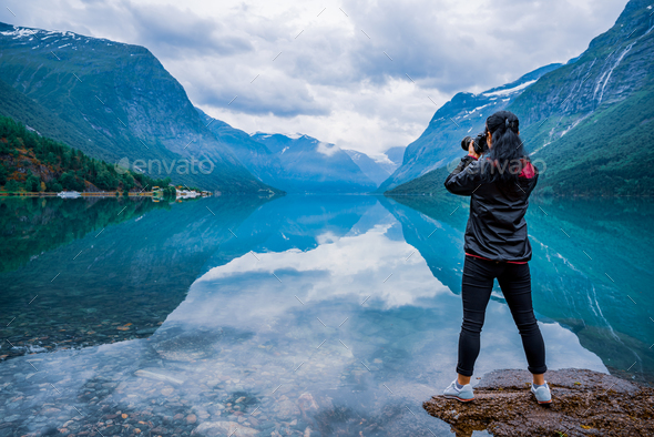 Nature photographer tourist with camera shoots lovatnet lake Bea - Stock Photo - Images