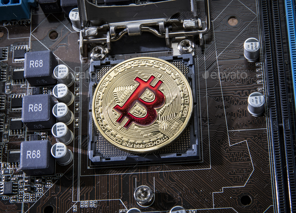 Gold Bit Coin BTC coins on the motherboard. Bitcoin is a worldwi - Stock Photo - Images