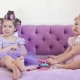 Two Little Girls in Curlers Talking Sitting on the Bed. Near Them Lies Cosmetics. - VideoHive Item for Sale