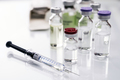 Vials of different size next to syringes at a hospital table, conceptual image - PhotoDune Item for Sale