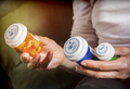 Woman examining medication treatment, several boats in the hand, conceptual image - PhotoDune Item for Sale