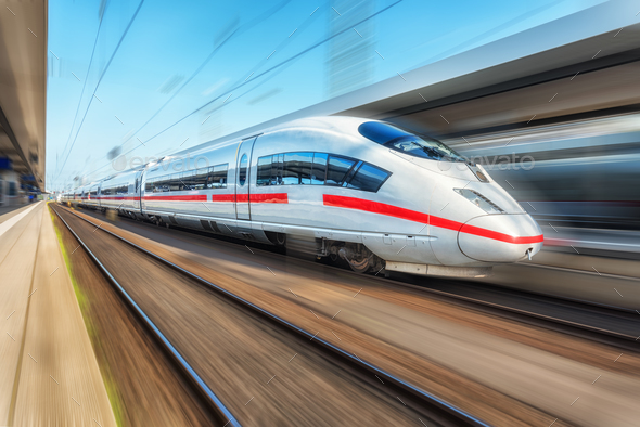 White modern high speed train in motion on railway station - Stock Photo - Images