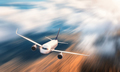 Modern airplane with motion blur effect is flying over low clouds