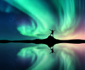 Northern lights and man near lake with reflection in water