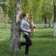 Young Man Plays the Saxophone. Man Is Standing on the Green Grass and Walking Among the Birches - VideoHive Item for Sale