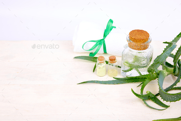 Aloe vera oil in glass bottle and towel for spa - Stock Photo - Images
