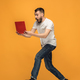 Image of young man over orange background using laptop computer while jumping. - PhotoDune Item for Sale