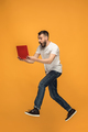 Image of young man over orange background using laptop computer while jumping.