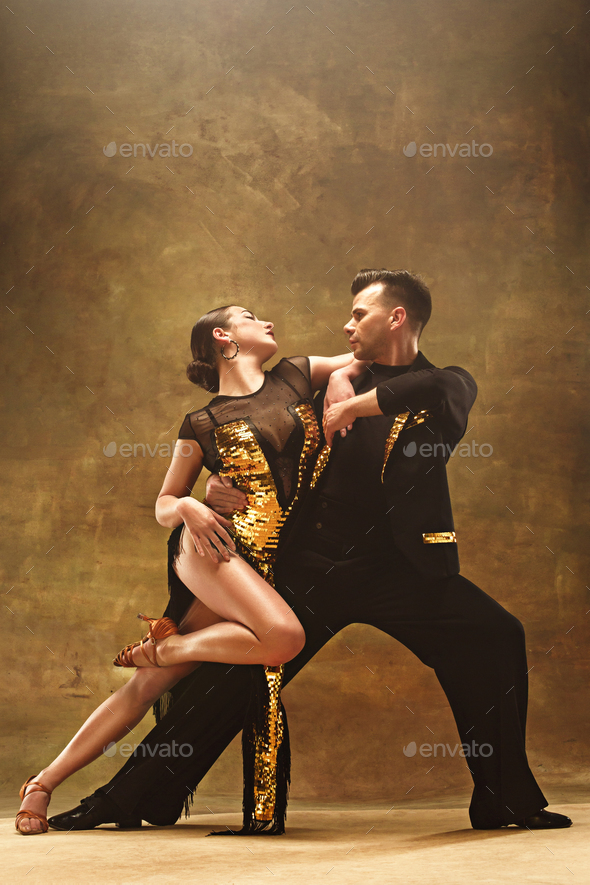 Dance ballroom couple in gold dress dancing on studio background. - Stock Photo - Images