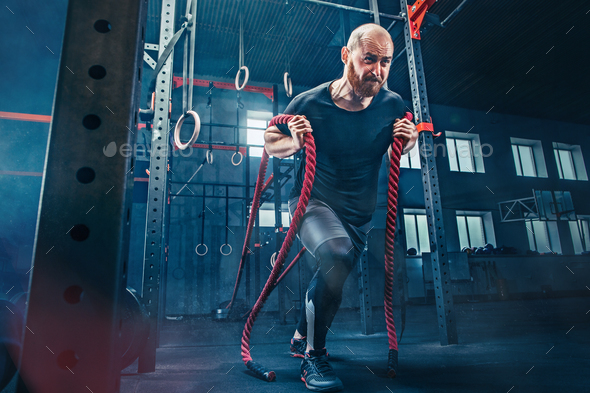 Men with battle rope battle ropes exercise in the fitness gym. CrossFit. - Stock Photo - Images