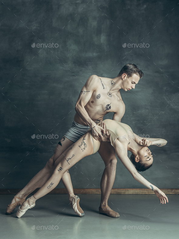 The young modern ballet dancers posing on gray studio background - Stock Photo - Images