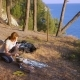 a Woman, the Campers, Cooks Food Next To a Tent on the Edge of a Steep Coastline in a Pine Grove - VideoHive Item for Sale