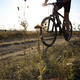Male cyclist driving by rural dirt road outdoors. Low angle view - PhotoDune Item for Sale