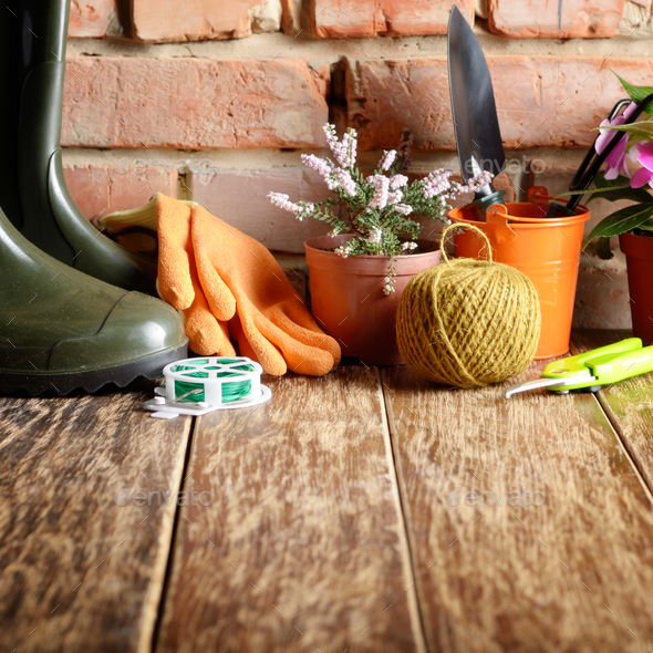 Gardening tools of shovel rake rope gloves on wooden floor - Stock Photo - Images