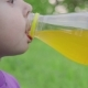 Girl Is Drinking Juice Outdoors in the Park,  Video - VideoHive Item for Sale