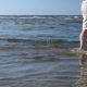 Man Walking on Shallow Water From Left To Right By the Sea on the Sand Beach - VideoHive Item for Sale