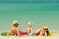 Family on beach. Toddler playing with mother and father. - PhotoDune Item for Sale
