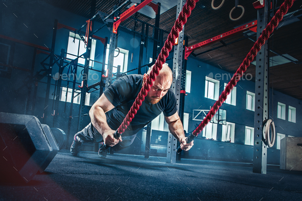Men with battle rope battle ropes exercise in the fitness gym. - Stock Photo - Images