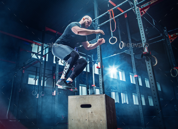 Man jumping during exercises in the fitness gym. CrossFit. - Stock Photo - Images