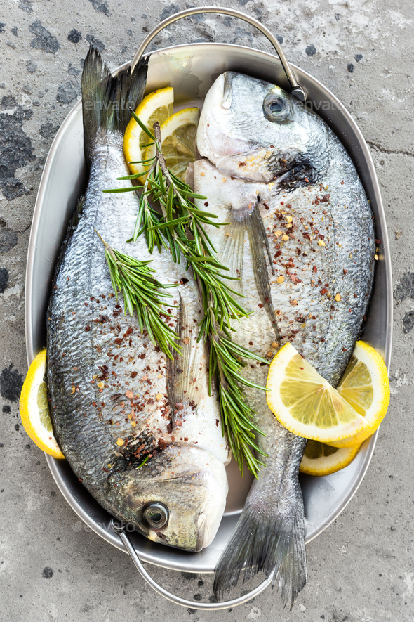 Fresh fish dorado. Raw dorado fish with lemon and rosemary. Sea bream or dorada fish - Stock Photo - Images
