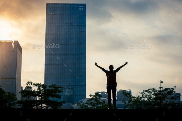 Woman open arms in the sunrise city - Stock Photo - Images