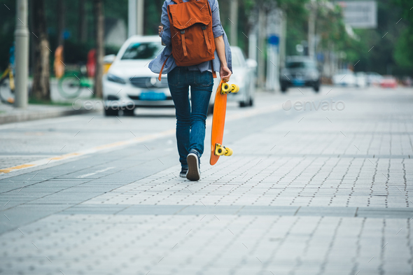Skateboarder with skateboard on city - Stock Photo - Images