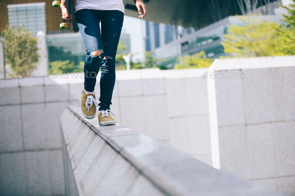 Young woman walking on the edge of a urban building wall at city - Stock Photo - Images