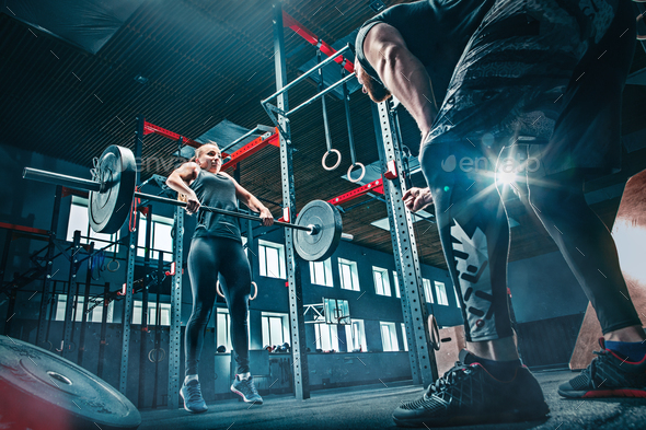 Fit young woman lifting barbells working out in a gym - Stock Photo - Images