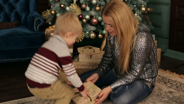 Mom and Son Open Christmas Gifts Near the Tree. by TYTARENKO | VideoHive