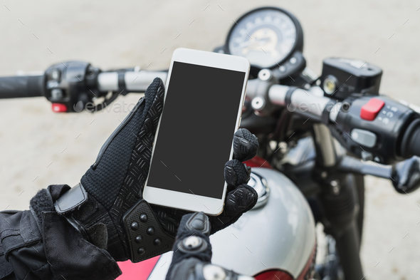 biker riding motorbike and holding smart phone - Stock Photo - Images