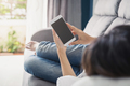 Young woman using smartphone at cozy home on sofa in living room - PhotoDune Item for Sale