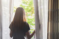 Young asian woman unveil curtain and looking out of window in the morning - PhotoDune Item for Sale