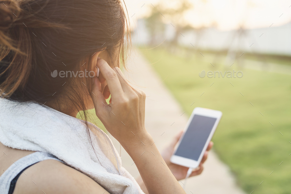 Female runner jogging and using smartphone to listening music in the park, Outdoor workout - Stock Photo - Images