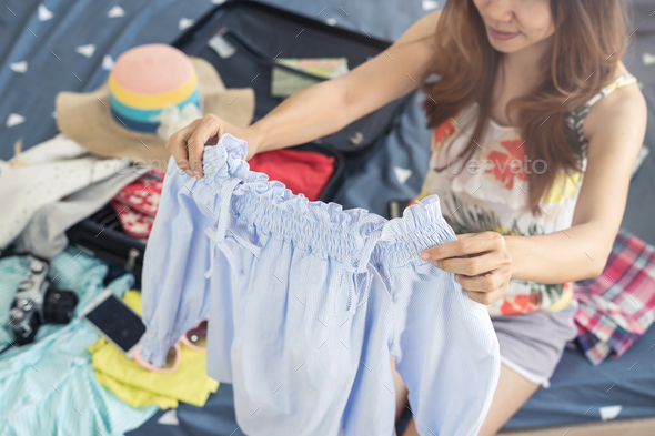 Young woman traveler packing her clothes and stuff in suitcase - Stock Photo - Images