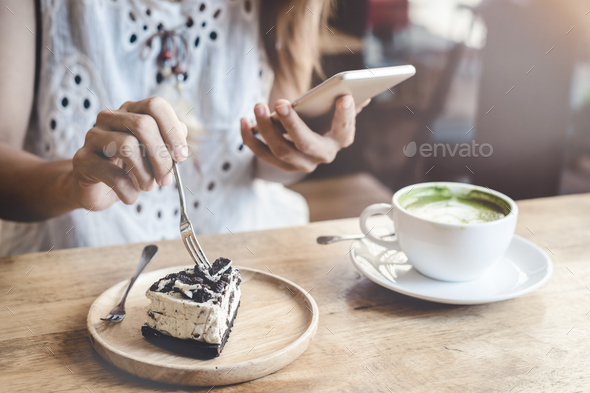Young woman using smart phone and eating cake - Stock Photo - Images