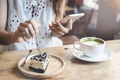 Young woman using smart phone and eating cake - PhotoDune Item for Sale