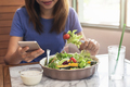 Young woman using smart phone and eating at restaurant - PhotoDune Item for Sale
