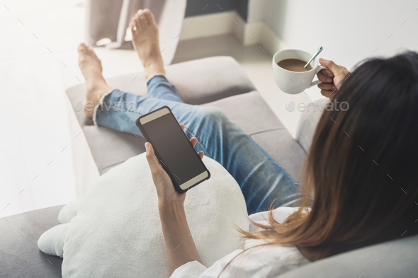 Young woman using smartphone at cozy home on sofa in living room - Stock Photo - Images