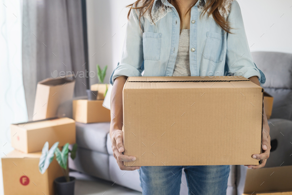 Young happy woman moving in new home and carrying cardboard boxes - Stock Photo - Images