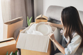 Young happy woman moving in new home and unpacking cardboard boxes - PhotoDune Item for Sale