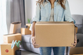 Young happy woman moving in new home and carrying cardboard boxes - PhotoDune Item for Sale