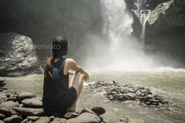 Young woman traveler looking at waterfall - Stock Photo - Images