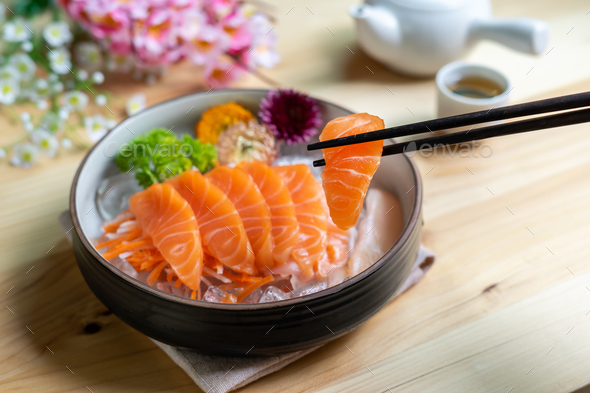 Salmon sashimi slice fresh serve on ice with tea, Japanese style - Stock Photo - Images