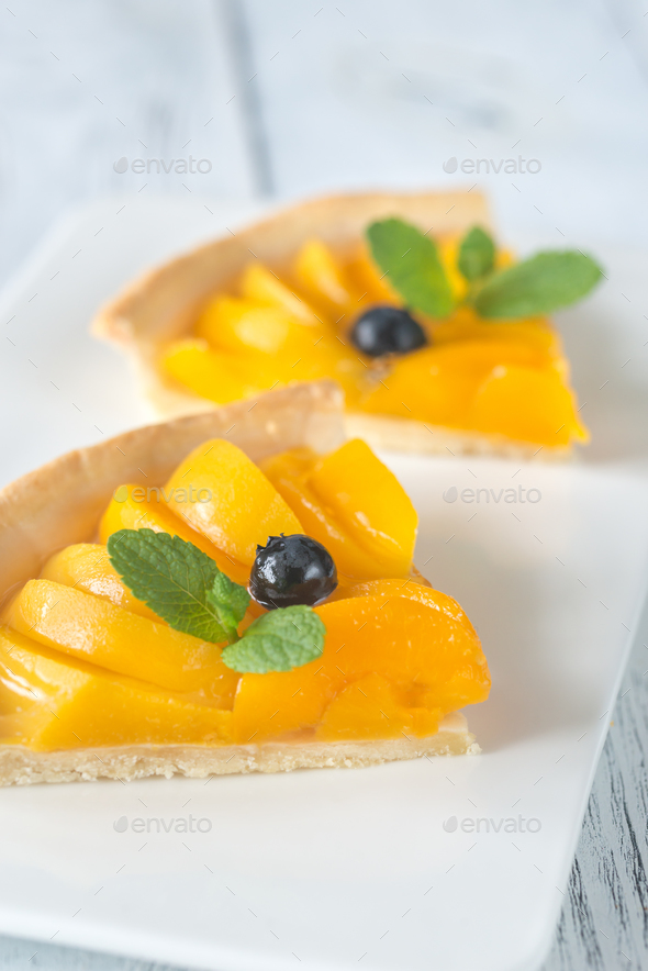 Slices of tart with peaches and blueberry - Stock Photo - Images